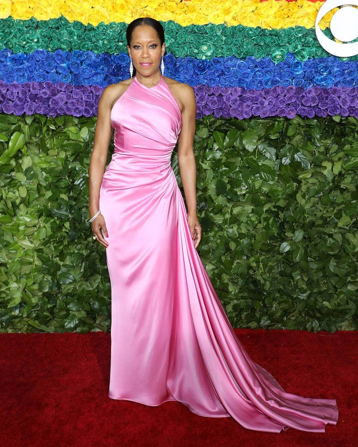 Regina King posing in a flowing gown at a Hollywood award show