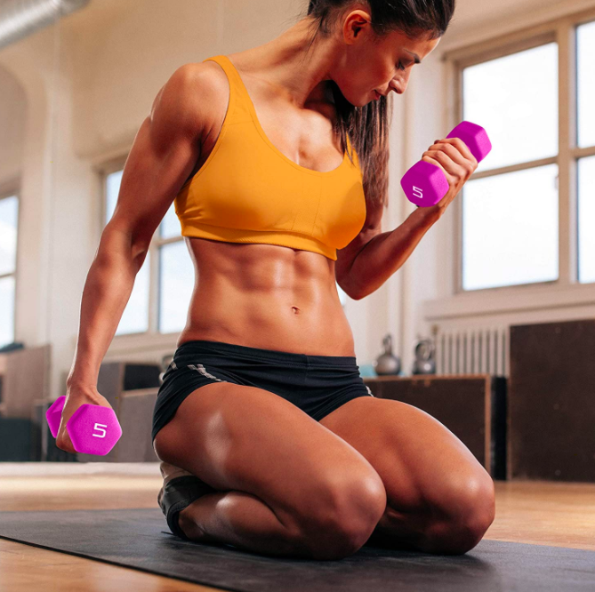 Model holds pair of pink 5-pound dumbbells in their hands while working out on a mat