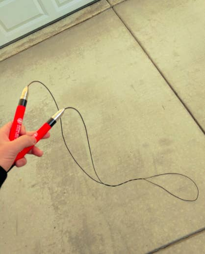 Reviewer holds red jump rope in hands before completing a workout