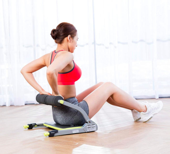 Model uses black and yellow Wonder Core compact exercise machine to crunch abs on hardwood floor