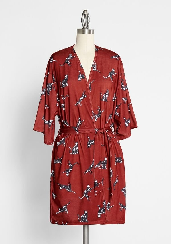 The burnt orange robe with a short hem and three quarter sleeves printed with skeleton black cats