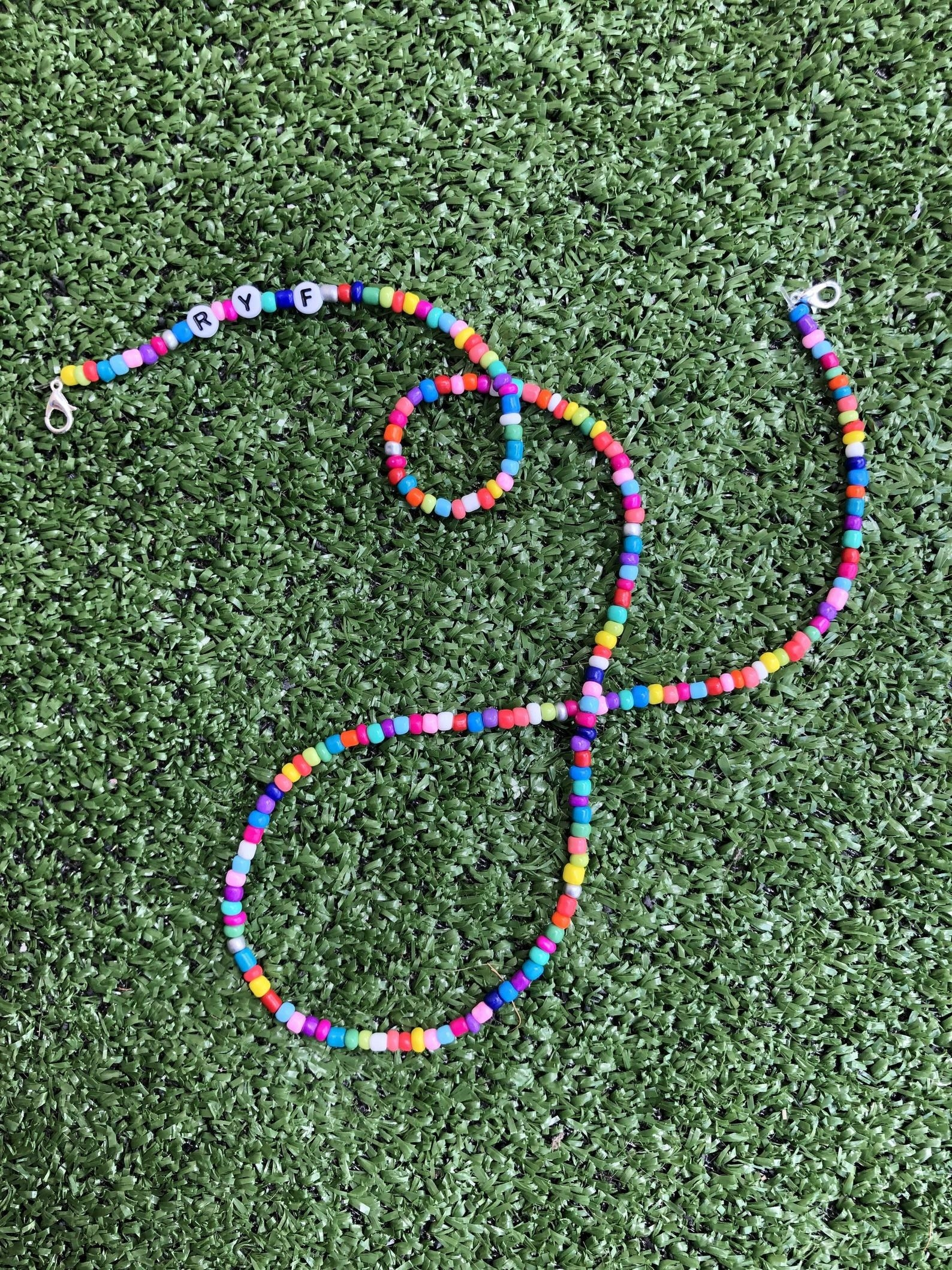 Rainbow beaded face mask chain with three beads that have letters monogrammed on it