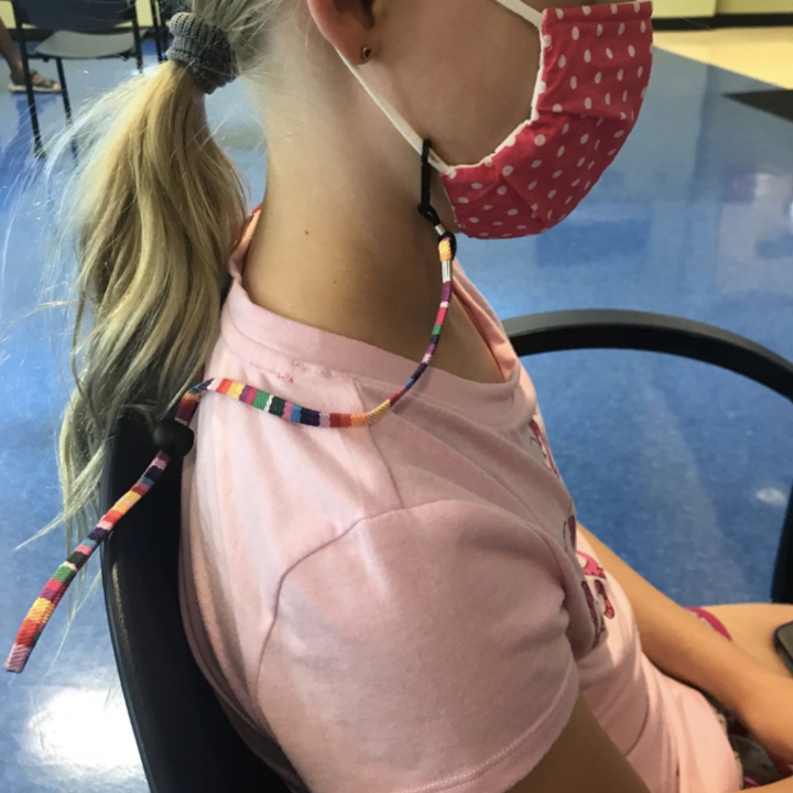 Reviewer in a multicolored lanyard attached to a mask