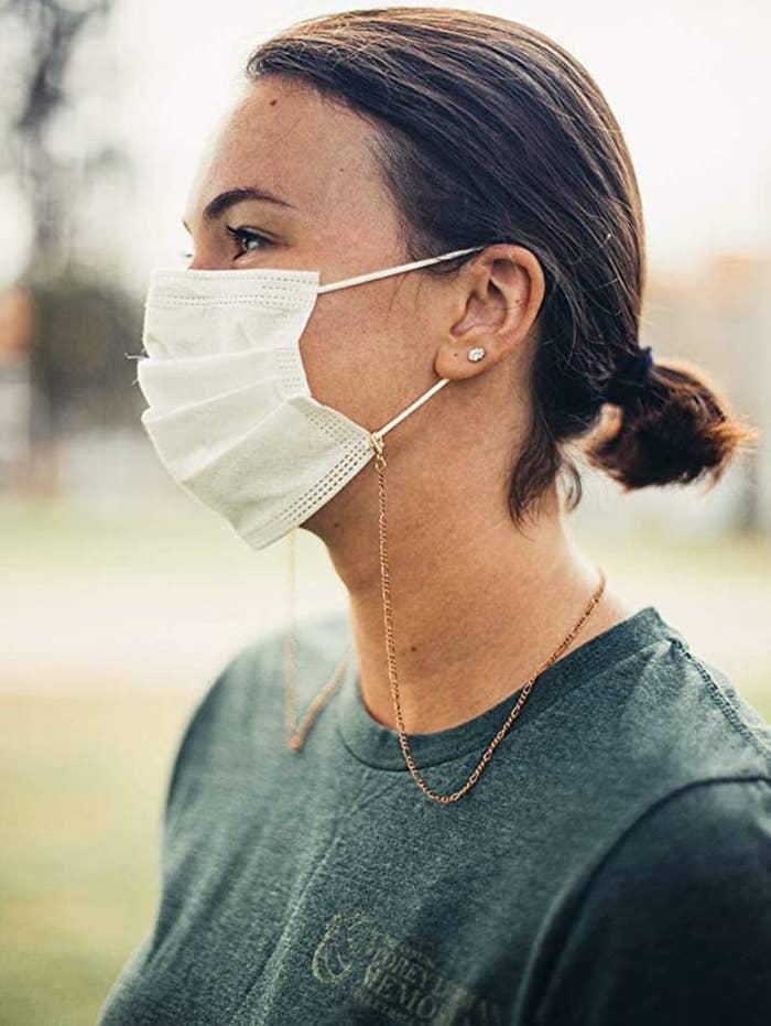 Model in a copper face mask chain
