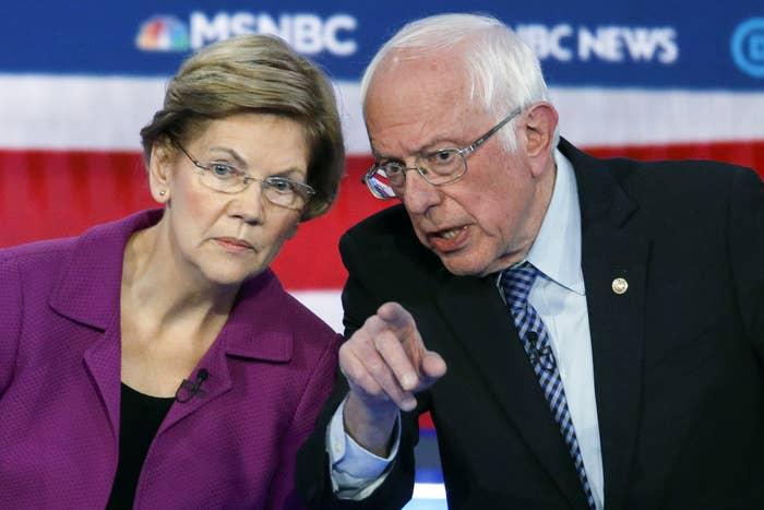Elizabeth Warren and Bernie Sanders lean toward each other at a Democratic debate