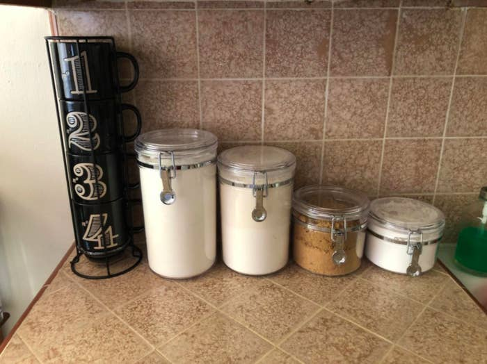 the four canisters on the counter filled up with baking items