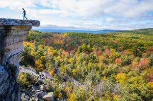 a man walks back towards land from the edge of a rocky white cliff; a forest of trees with fall colors lies beneath