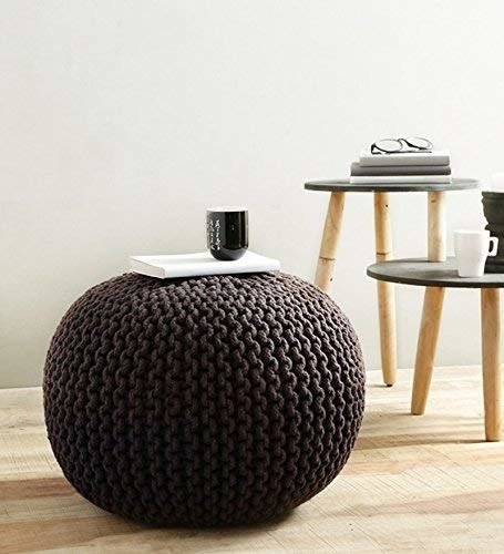 A woven black pouf next to a table