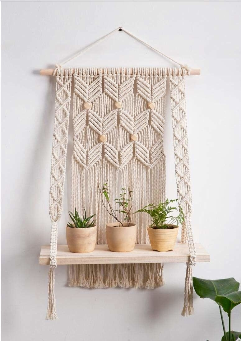A macrame wall hanging with 3 plants on a wooden shelf