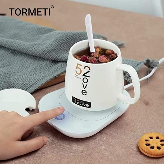 Mug warmer with some tea in it on a table.
