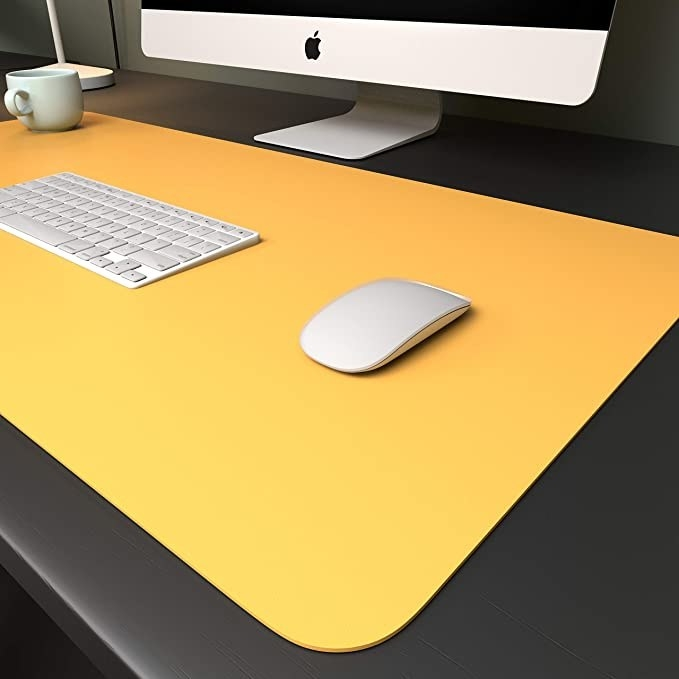 Yellow desk pad with a keyboard, mouse and mug on it.