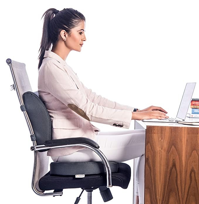 A woman sitting at her desk on the memory foam cushion.