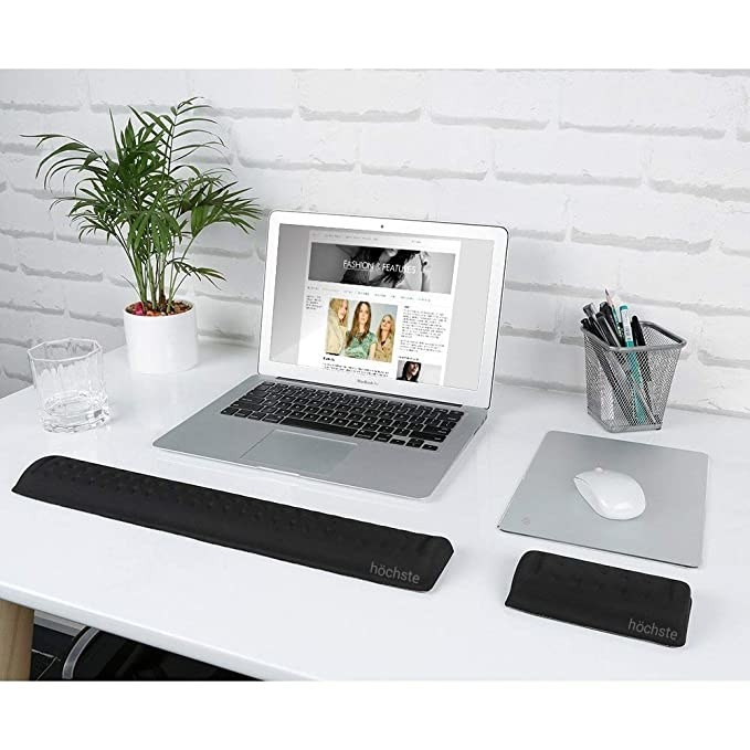 A work desk with a laptop and mouse pad on it, and some water and plants around it. The wrist support is placed in front of the laptop.
