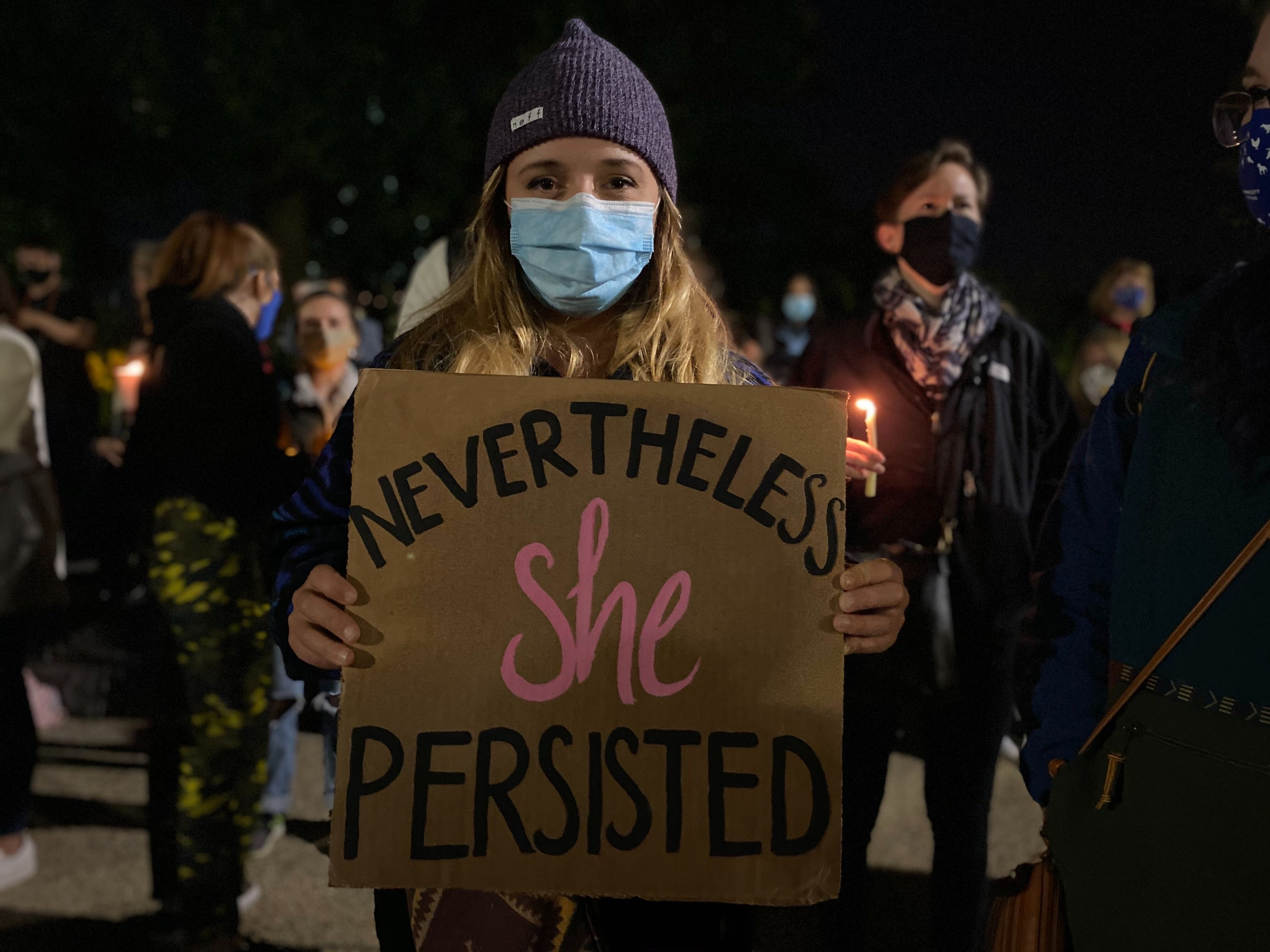 "A woman wearing a beanie and a face mask holds a sign that reads ""Nevertheless she persisted"""