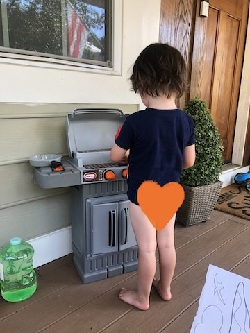 A toddler plays at his toy grill during the first day of potty training.