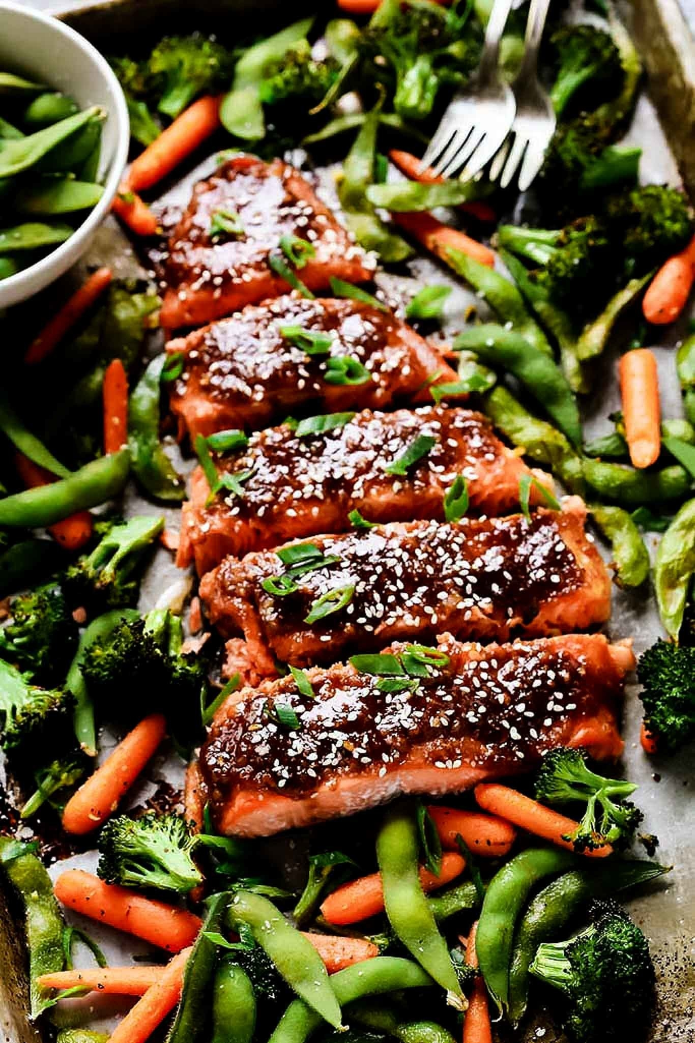 A sheet pan topped with glazed miso salmon, edamame, carrots, and broccoli.