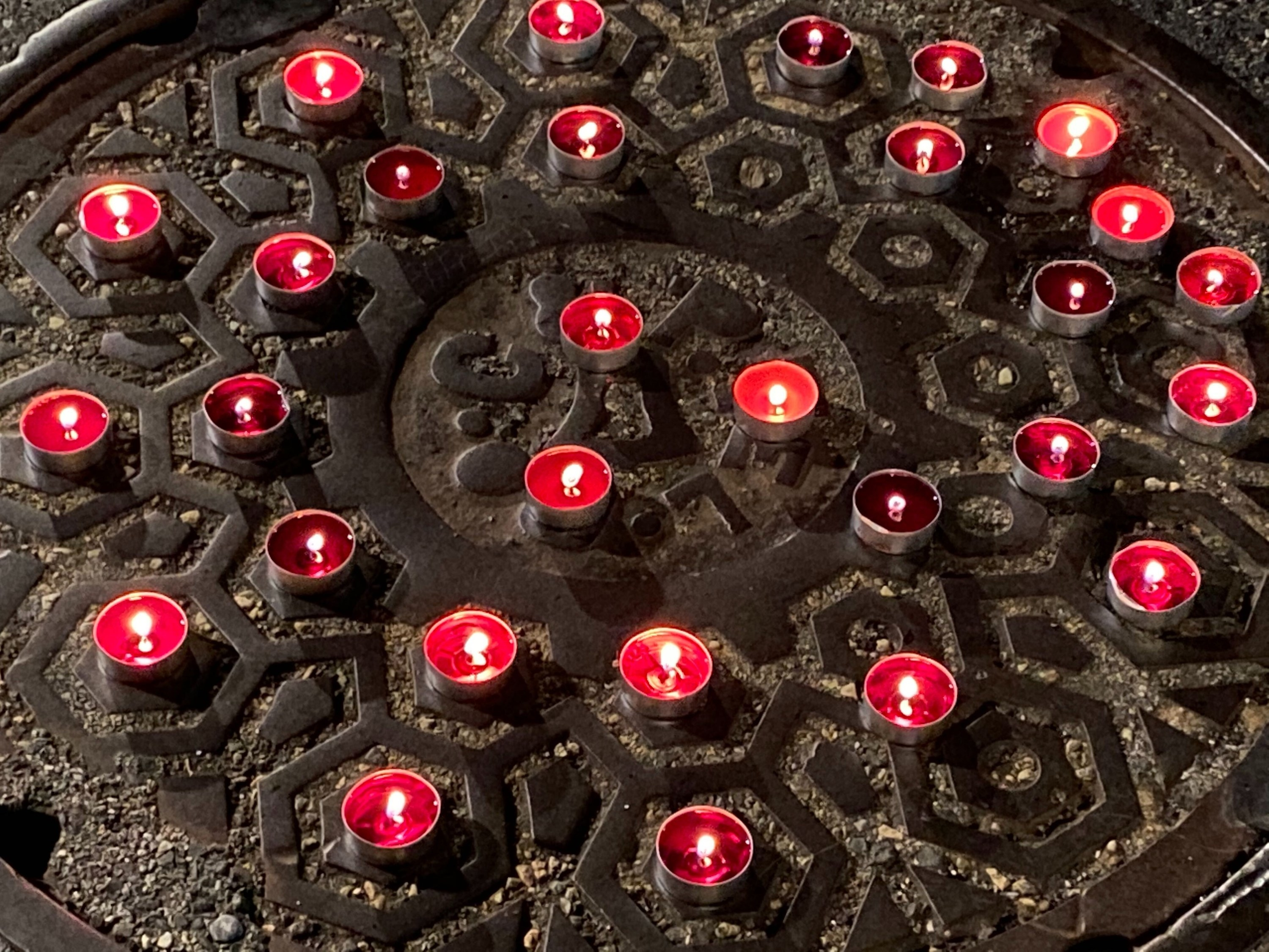 A small vigil of red candles burning atop a sewage manhole cover