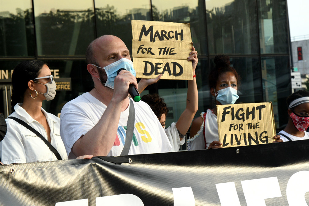 "Protesters wearing masks hold signs reading ""March for the Dead"" and ""Fight for the living."""