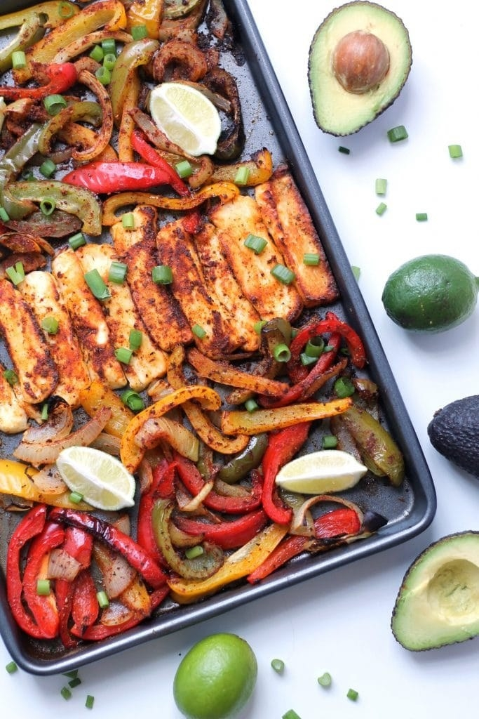 A sheet pan with crispy sliced haloumi, peppers, onion, and lime wedges.