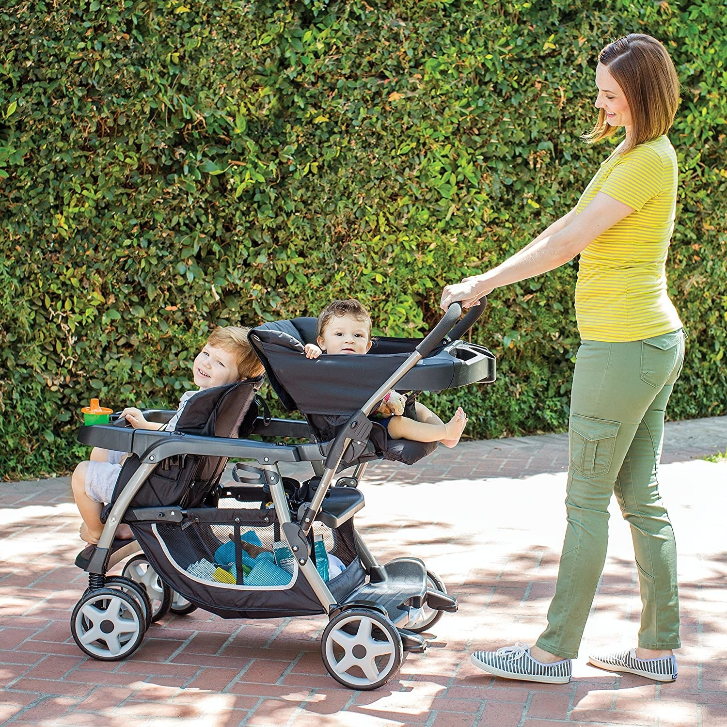 A parent pushing two kids in the double stroller