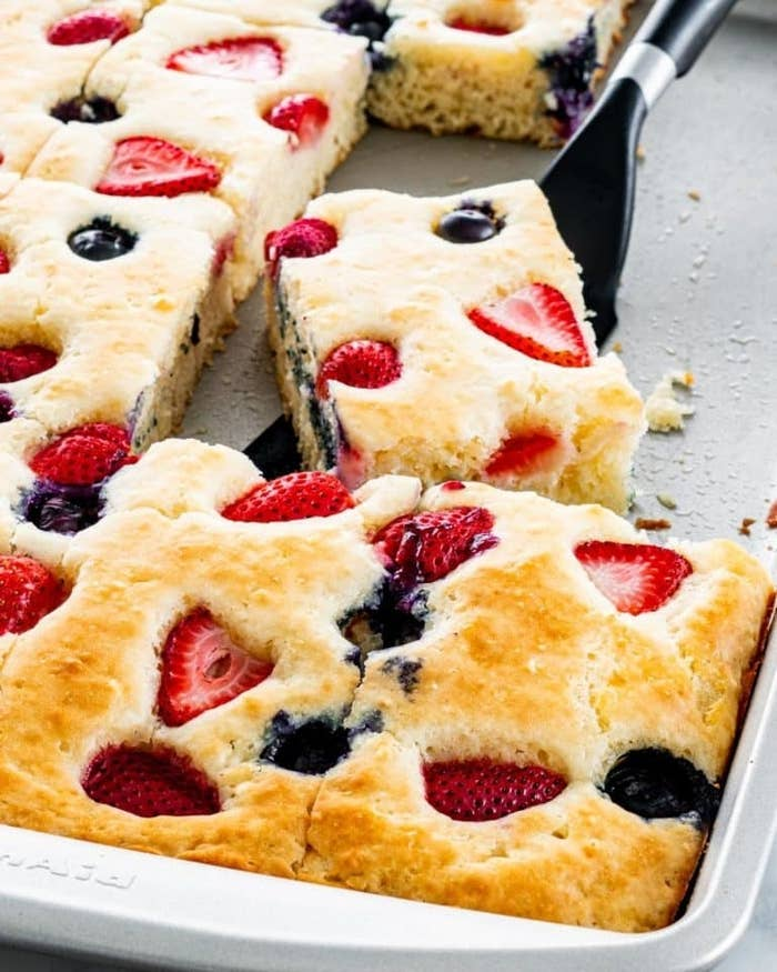Sheet pan pancakes filled with strawberries and blueberries being sliced into squares.