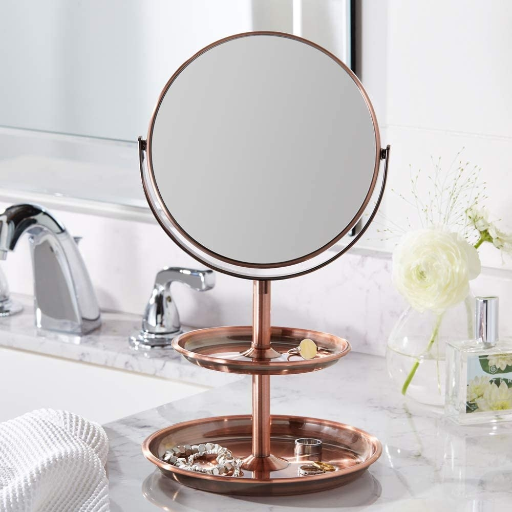 The mirror on top of a bathroom counter with jewelry in the ring dishes