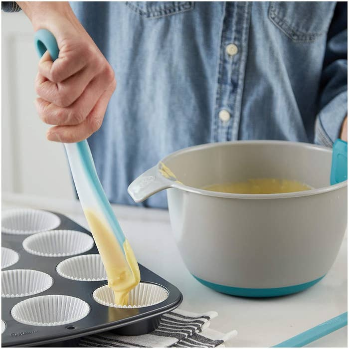 A person squeezing the spatula and scooping cupcake batter into a muffin tin