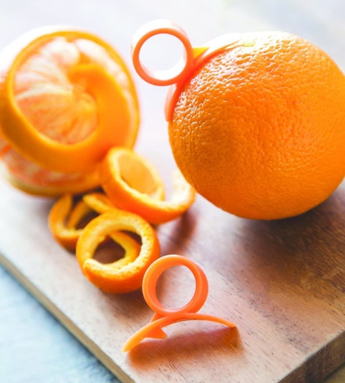 A peeled orange and an orange wit the peeler dug into it on a cutting board