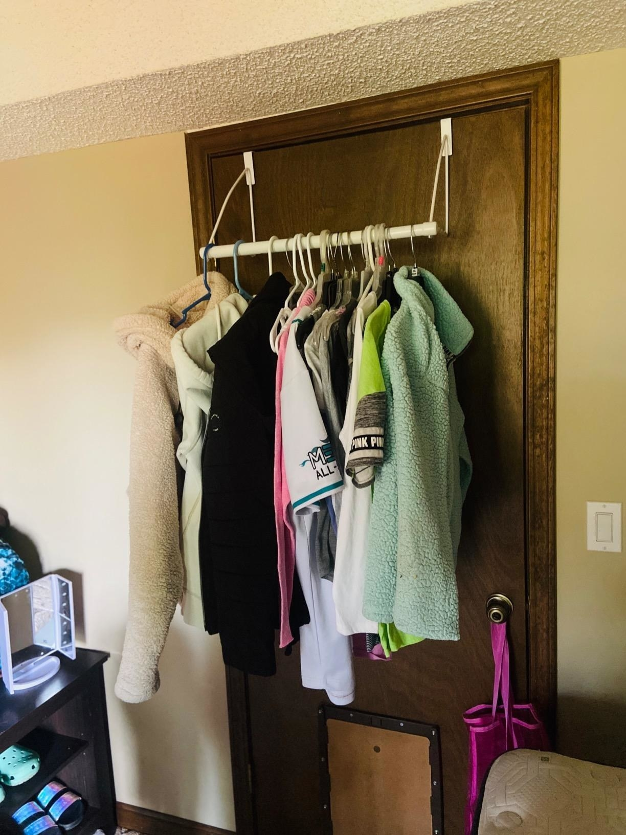 Reviewer pic of the white rack on the back of the door with clothes hanging from it.