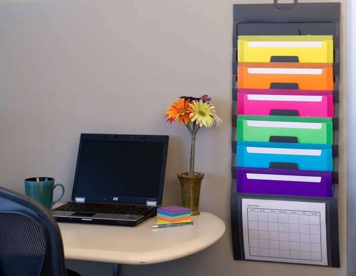 The colorful organizer hung next to a desk with a computer and flowers