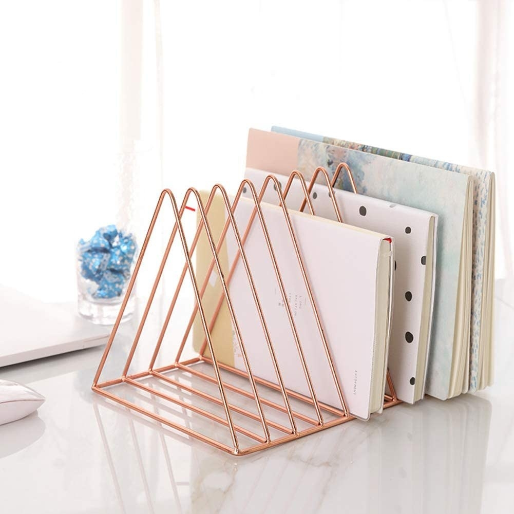 The rose gold triangle-shaped sorter with four different-sized notebooks in it