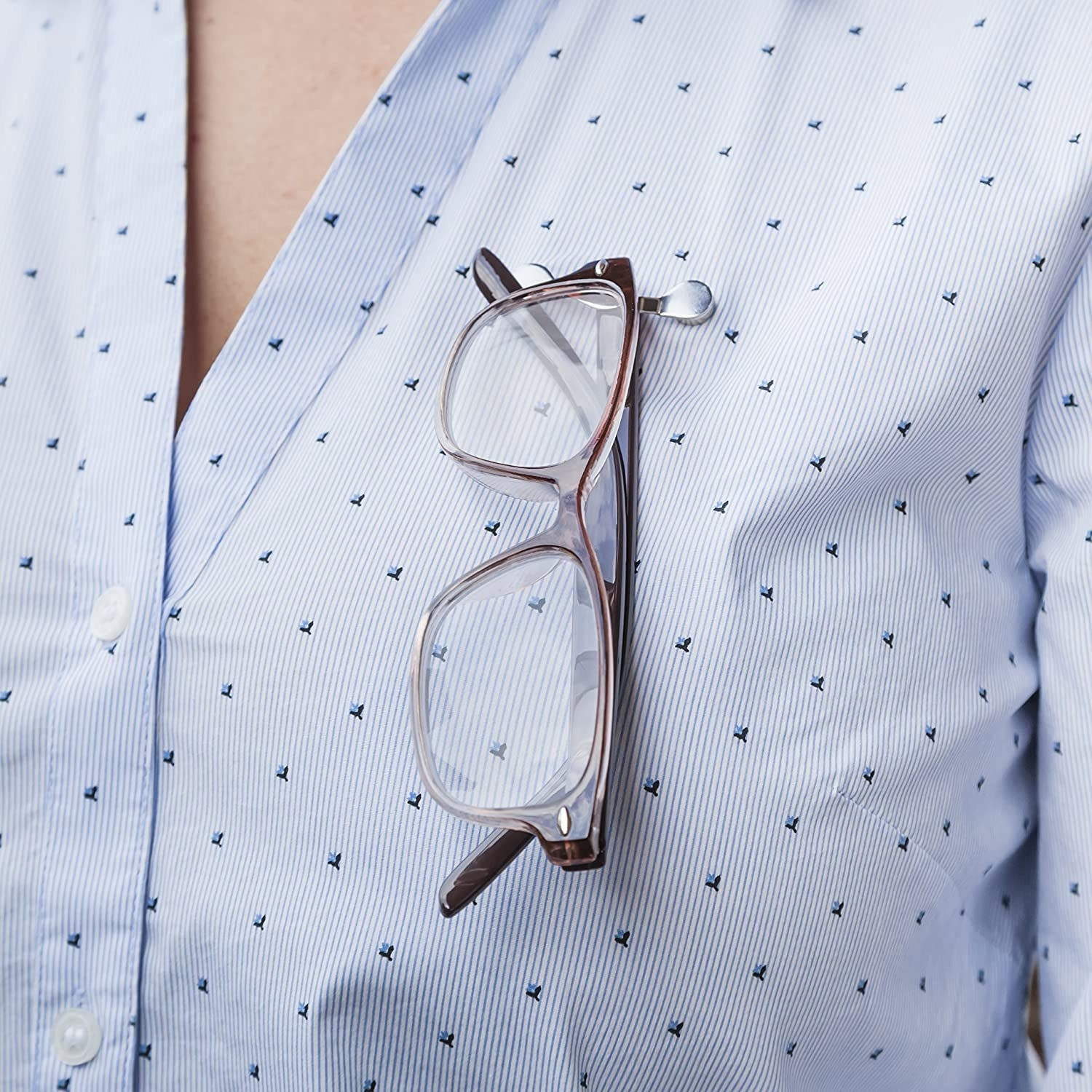 A pair of glasses hanging from a clip attached to a person's button up shirt