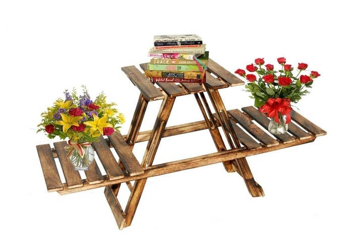 A table with three platforms similar to a picnic table, with flower vases on two ends and books piled on the main table.