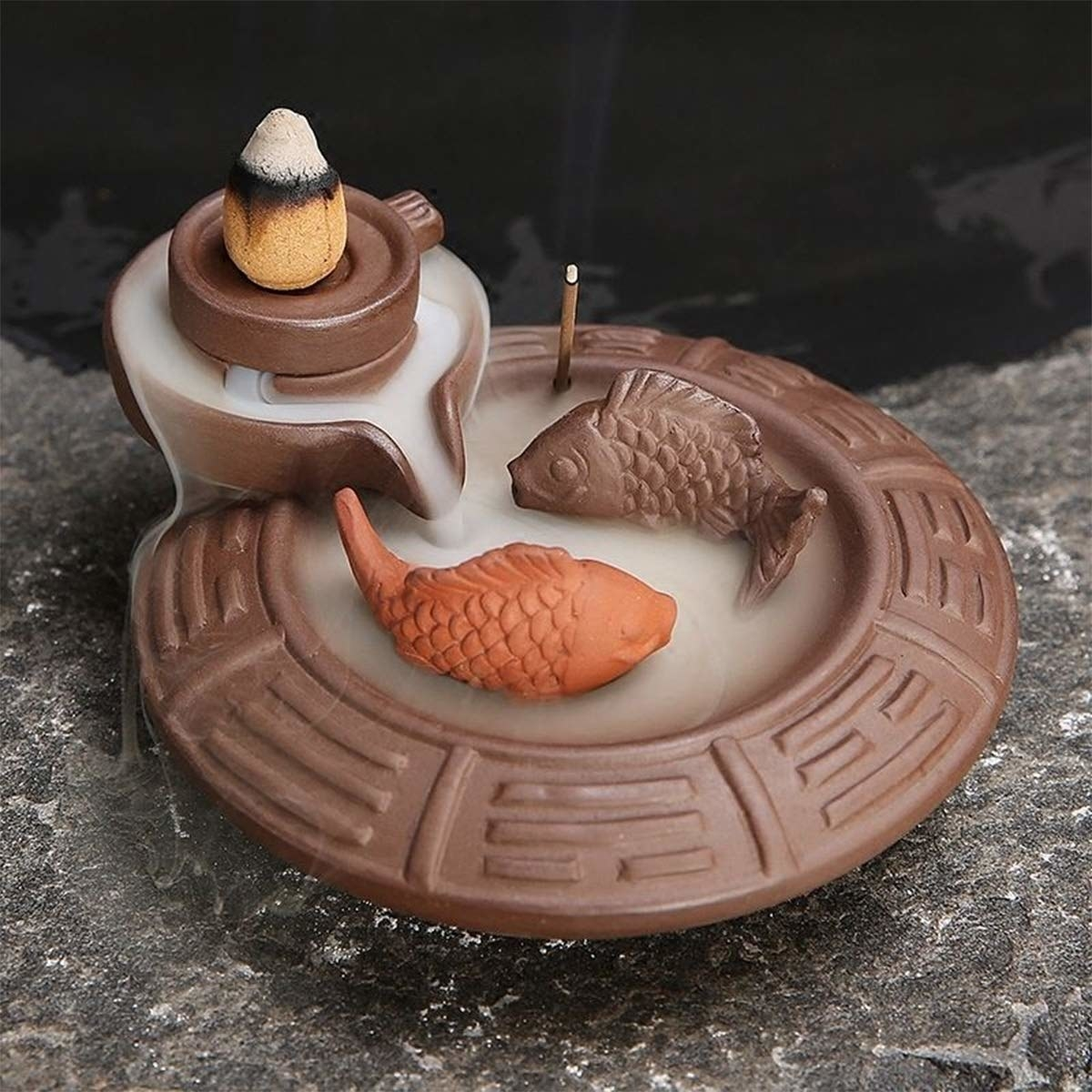An incense burner with two fishes swimming inside, where smoke deposits to form a sort of pond.