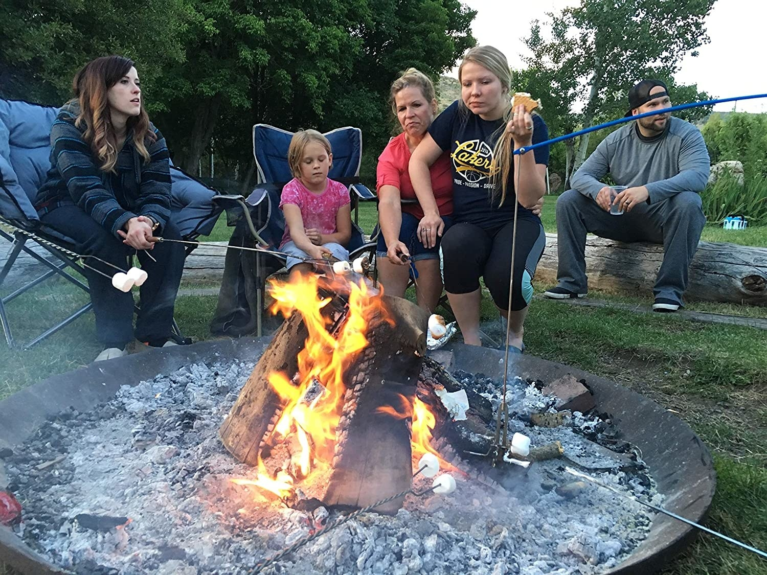 Five people sitting in front of a fire pit roasting marshmallows