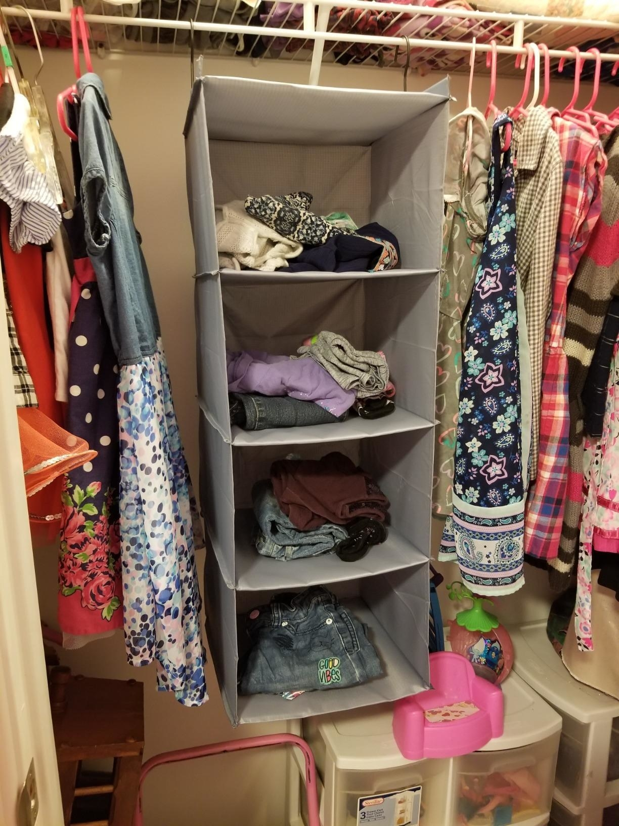 Reviewer pic of the four-tier cubby hanging in a closet with clothes folded in each one.