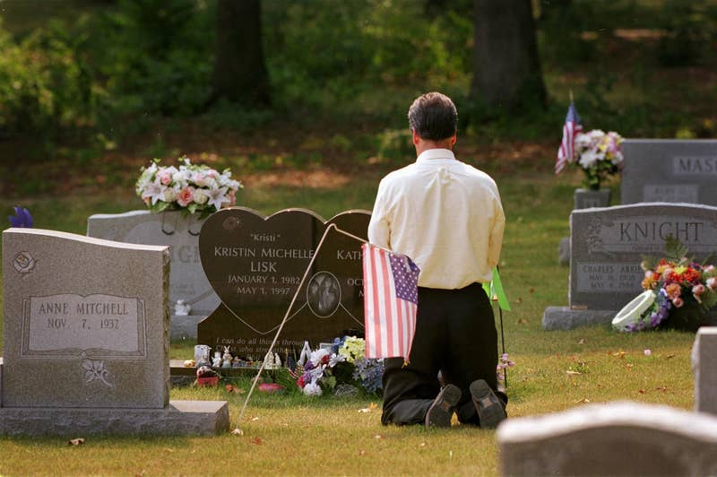 A male FBI agent in a white shirt kneels in a graveyard in front of the heart-shaped tombstone of the Lisk sisters.