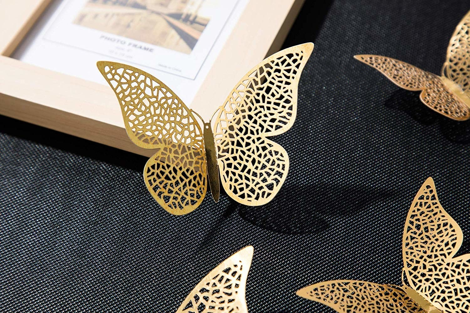 A 3D butterfly placed on a photo frame, with corners of other butterflies visible.