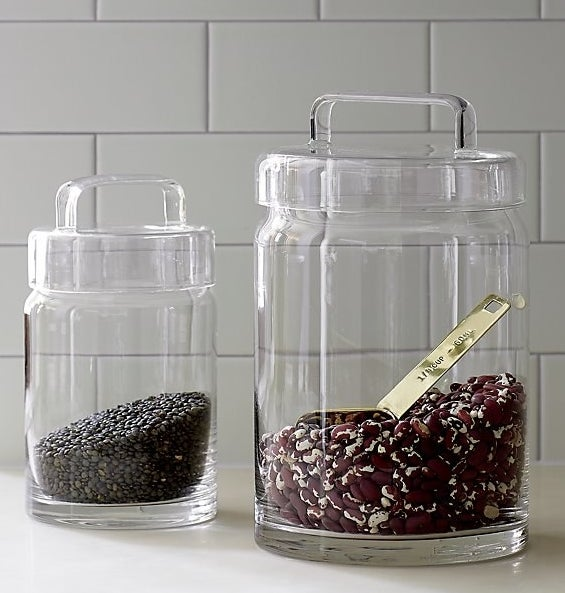 one large and one medium glass jar with glass lids full of dry rice and a scooper
