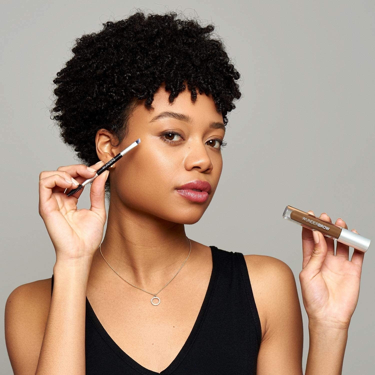 A person holding a tube of brow gel in one hand and a small makeup brush in the other