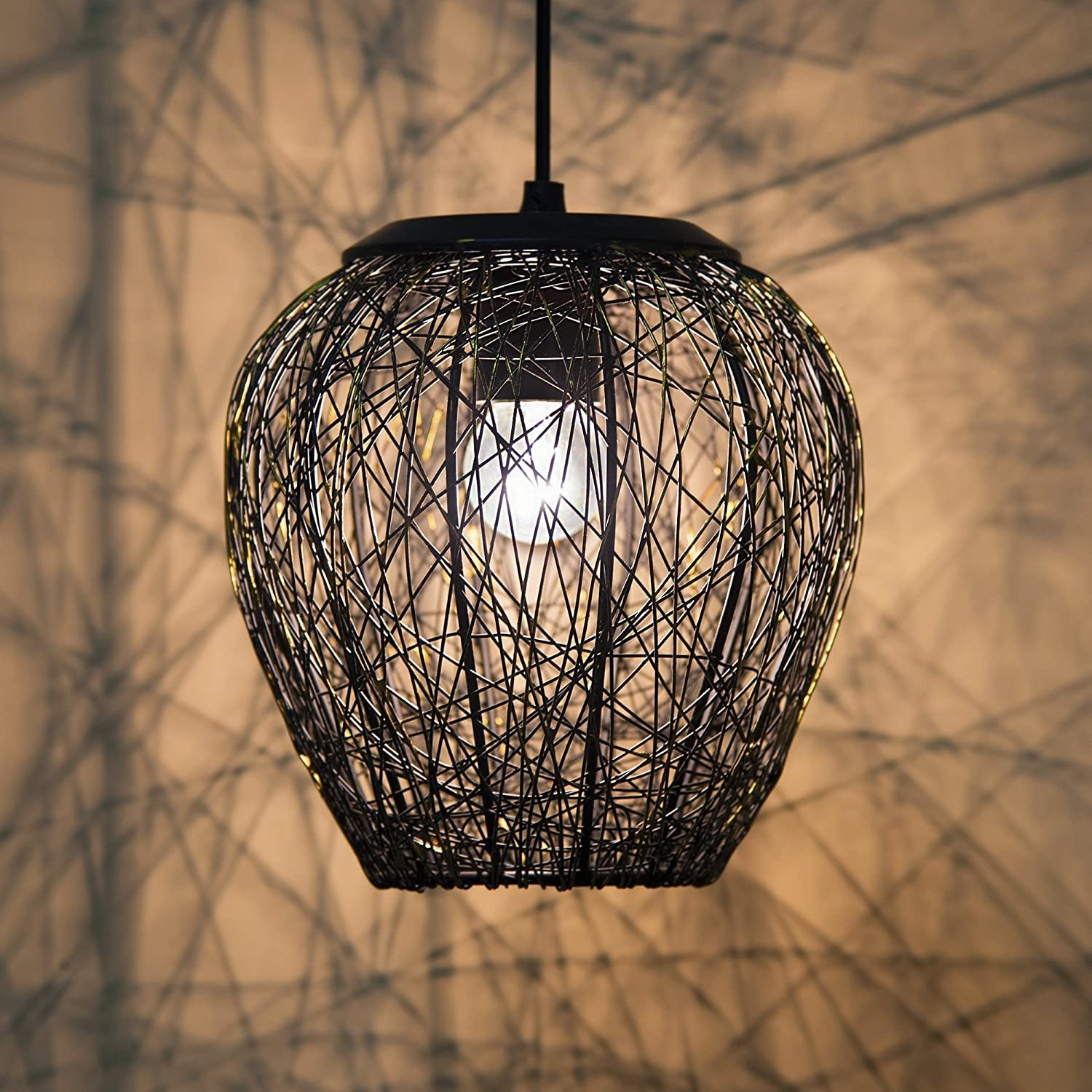 A lit up mesh chandelier throwing patterns on the wall behind it.