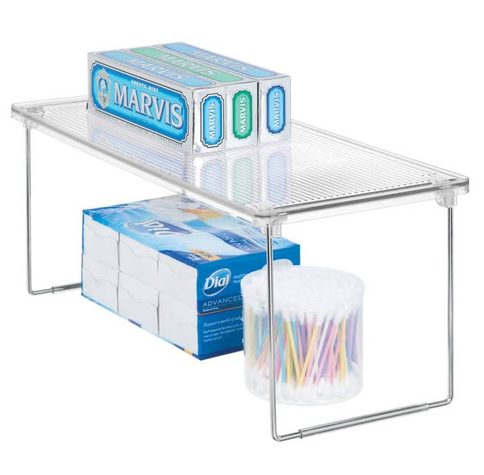 The clear storage shelf being used to hold toothpaste,  Q-tips, and soap
