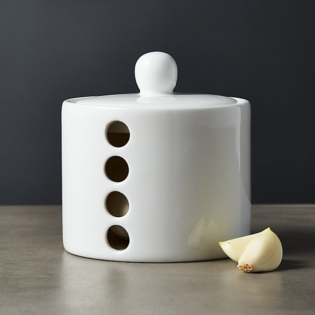 small white ceramic jar with lid and holes down the side