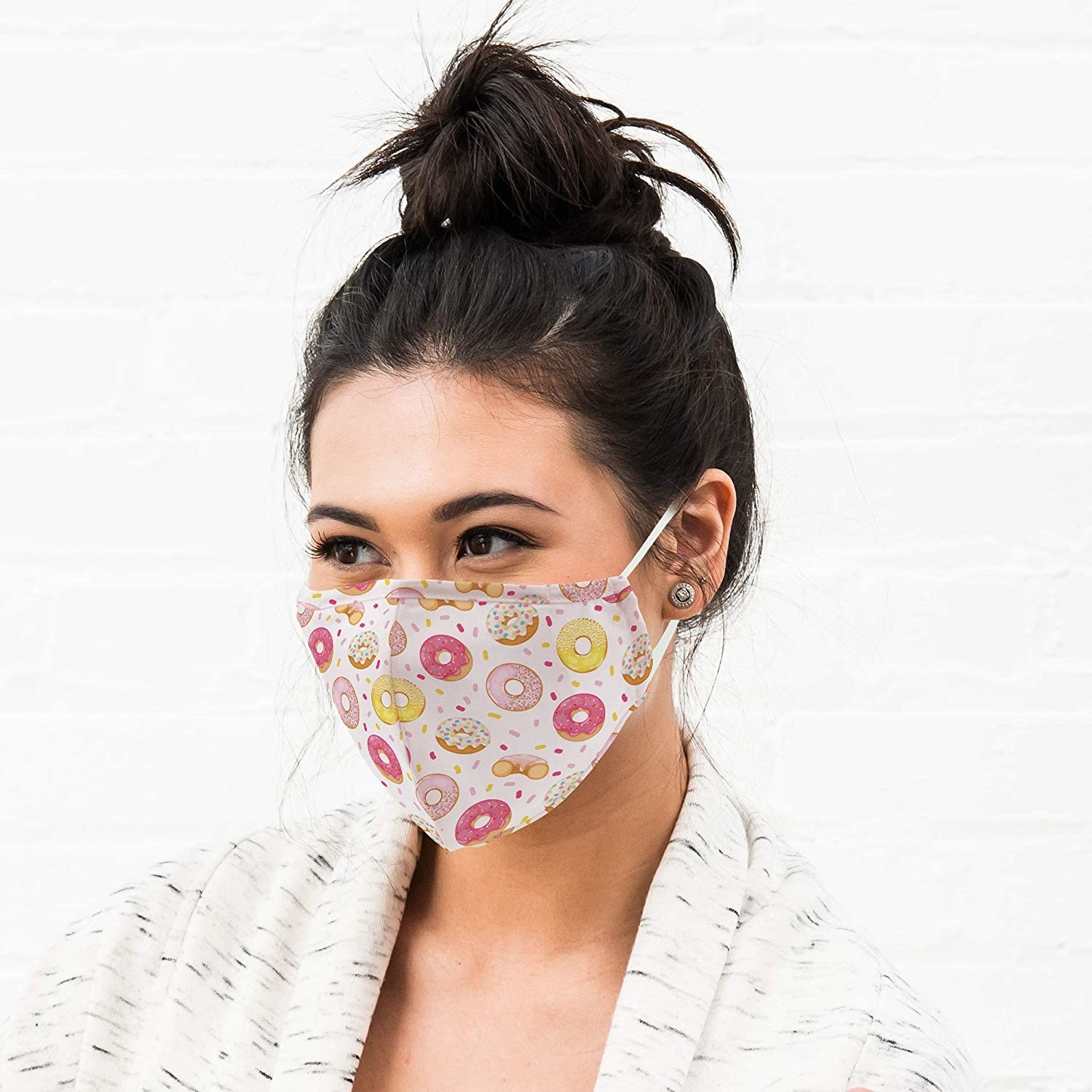 A person wearing a mask covered in donuts