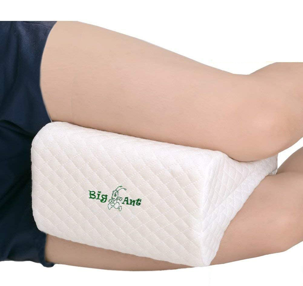 A person sleeping on their side with a small pillow between their thighs