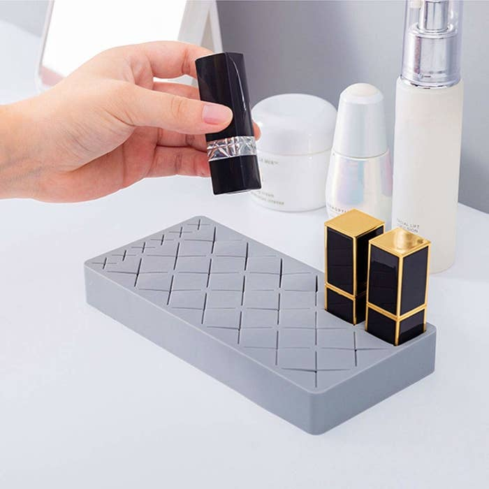 The grey rectangle holder with xs all over it and two tubes of lipstick in the corner with a hand about to put a third tube in it