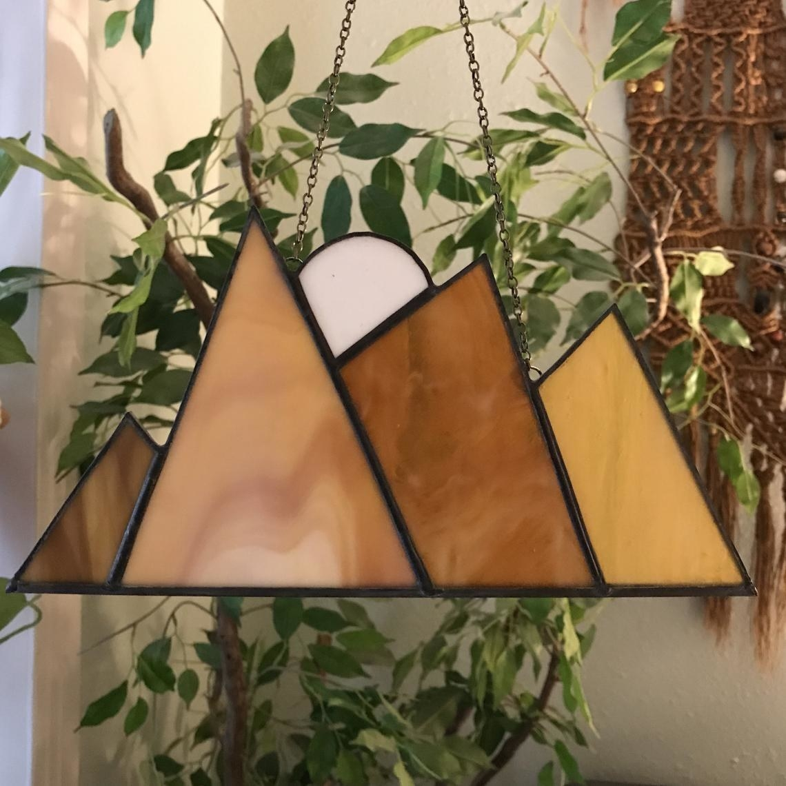 Small stained glass wall hanging with four triangular mountains in varying sizes and a half moon at the peaks