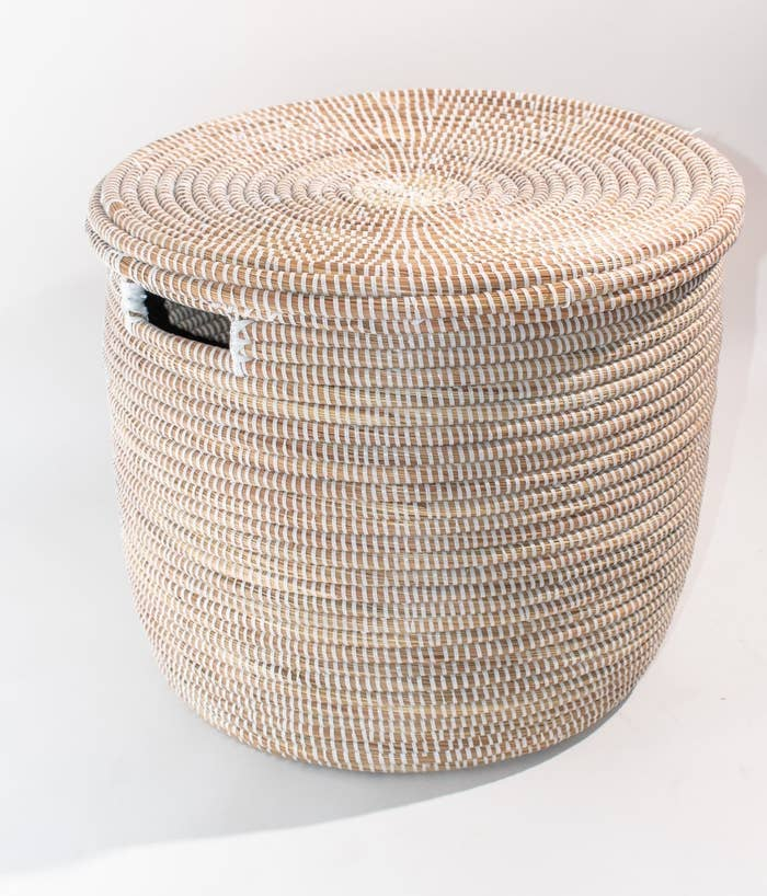 The tan basket with white thread and a rectangular hole on the side for handles with a matching lid