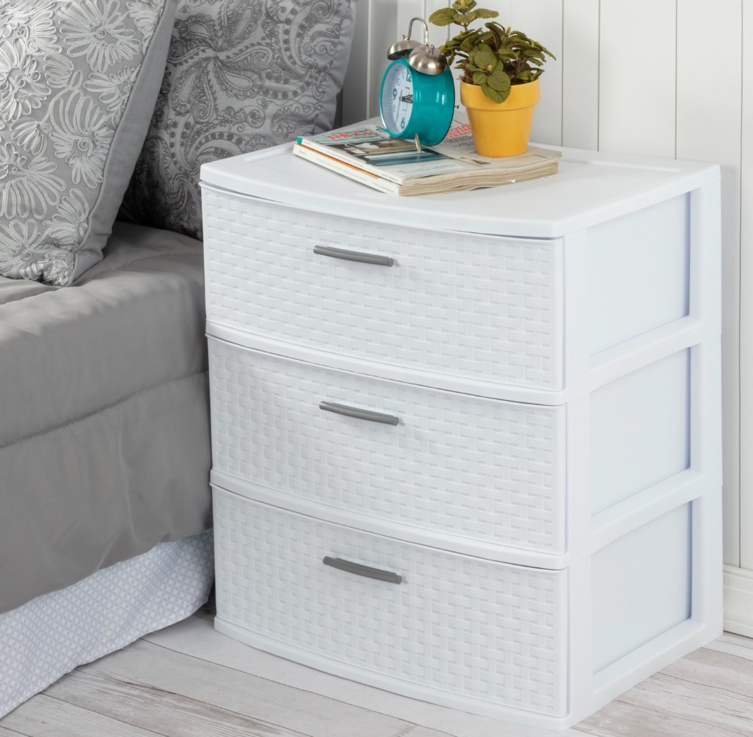 The three drawer tower in white with a plant and alarm clock on top