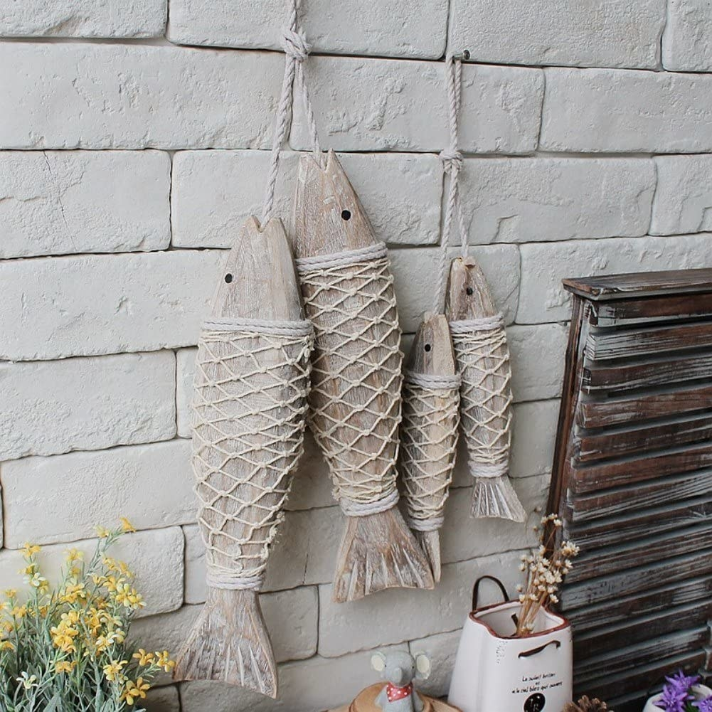 Four wooden fish with thin rope netting around their bodies, hung up with the same net rope